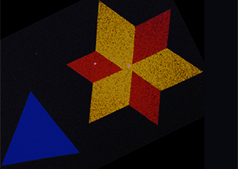 A false-color electron microscopy image showing the star-shaped crystals in monolayers of two-dimensional semiconducting molybdenum disulfide. The red, yellow, and blue colors represent two dominant crystal orientations that are stitched together by a line of atomic defects. —Image courtesy of Pinshane Y. Huang and David A. Muller